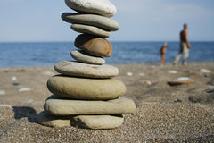 Pebble. Balanced stones on a beach with people stock images