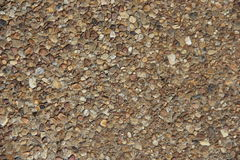 Pebble Aggregate Background. A section of exposed aggregate stone, with many pebbles in shades of brown, white, cream and black. Good background Royalty Free Stock Image