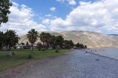 Pebble Beach на Gulf of Corinth, пальмы, море, горы, Стоковые Фотографии RF
