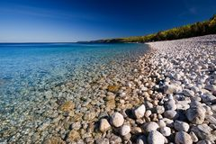Pebble Beach. White pebble beach and crystal clear lake Royalty Free Stock Image