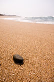 Pebble on the beach. A single black rock lying on the beach with waves in the background Royalty Free Stock Photo