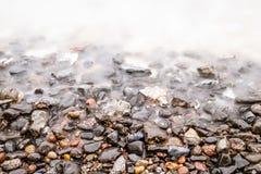 Pebble Beach avec les vagues lisses Photographie stock