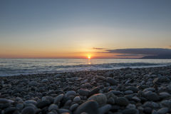 Pebble beach at beautiful sunset. Distant mountains in clouds Stock Photography