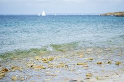 Pebble beach, with blue sea and white boat in the background. Photographed in Glenan Isles France Royalty Free Stock Photography