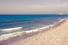 Pebble beach and blue water of the Mediterranean Sea. Toned Stock Photo
