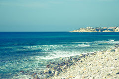 Pebble beach and blue water of the Mediterranean Sea. Toned Stock Photography