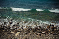 Pebble beach and blue water of the Mediterranean Sea. Toned Stock Image