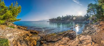 Pebble beach on Brac island with pine trees and turquoise clear ocean water, Supetar, Brac, Croatia.  stock images