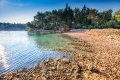 Pebble beach on Brac island with pine trees and turquoise clear ocean water, Supetar, Brac, Croatia.  stock image