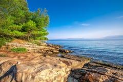 Pebble beach on Brac island with turquoise clear ocean water, Supetar, Brac, Croatia. Stone beach on Brac island with turquoise clear ocean water, Supetar, Brac stock photo