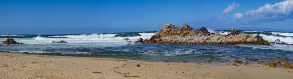 Ocean Water Explosions. Pebble Beach, California, February 19, 2018:  Wave action on a clear and blustery day produces water explosions against the rocky Royalty Free Stock Photo