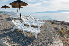 Pebble beach with chaise-longues and umbrellas Royalty Free Stock Photography