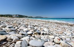 Pebble beach with clear blue water on Rhodes island, Greece.  Royalty Free Stock Photography