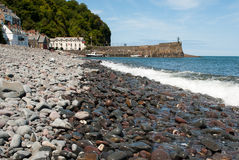 Pebble Beach with Clovelly, UK in the background Royalty Free Stock Images