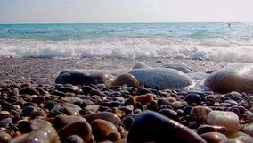 Pebble Beach con i piccoli ciottoli e spuma del mare La barca è sul mare La superficie del mare su un Pebble Beach selvaggio Le o stock footage