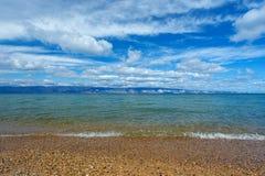 Pebble Beach de la isla de Olkhon, el agua pura de la turquesa del lago y del cielo azul fotografía de archivo libre de regalías