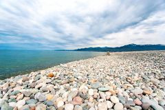 Pebble beach with dramatic cloudy blue sky background in Batumi. Georgia, Caucasus. Multicolored outdoors horizontal image with perspective. Low point of view royalty free stock photography