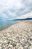 Pebble beach with dramatic cloudy blue sky background in Batumi. Georgia, Caucasus. Multicolored outdoors vertical image with perspective stock photography