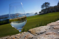 Glass White Wine Reflection Pebble Beach Golf. Glass of white wine reverse reflection of golf course with gently blurred background of ocean and course greens stock images