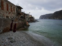 Pebble beach in Greece. Two umbrellas on a pebble beach in an old Greek fishing village Stock Photo