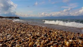 Pebble beach of Lake Baikal in autumn. Landscape. Sea shore, splashing waves. Pebble beach of Lake Baikal in autumn. Beautiful landscape: sea shore, splashing stock footage