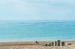 Pebble Beach le jour lumineux avec les poteaux en bois menant à la mer Images libres de droits