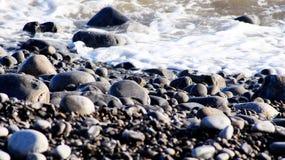 Pebble Beach mit ruhigem schäumendem Wasser Lizenzfreie Stockfotos