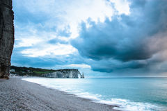 Pebble beach in Normandy coast in France. View of a pebble beach in Normandy coast in France with a heavy couldy sky stock photo