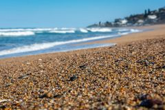 Pebble beach with the ocean break as a background royalty free stock photos