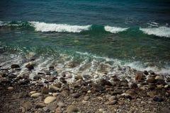 Pebble Beach och blått vatten av medelhavet tonat Fotografering för Bildbyråer