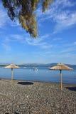 Pebble Beach och slags solskydd i Grekland Royaltyfria Bilder
