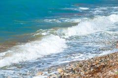 Pebble Beach och små vågor Arkivbilder