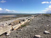 Pebble beach with old sea defence in Wales United Kingdom. Old sea defence in North Wales with Snowdonia in distance UK Royalty Free Stock Photos