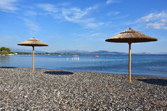 Pebble beach and parasols in Greece. Pebble beach and parasols in Paralia Politikon, boats in Aegean sea on background, Greece Stock Photos
