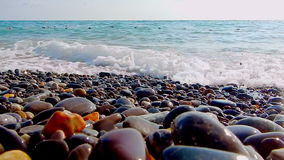 Pebble beach with small pebbles and sea surf. The boat is on the sea. The surface of the sea on a wild pebble beach. The waves are stock video footage