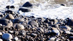 Pebble beach with still foaming water. The Knap pebble beach in Barry next to Barry Island. The water is still on the shore Royalty Free Stock Photos