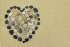 Pebble beach stone heart on golden sand Stock Image