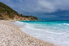 Pebble Beach, stormigt blått hav, grön kulle och grå färghimmel i Dominikanska republiken Royaltyfria Foton