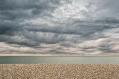 Pebble beach and stormy skies over English channel. Peeble beach and a grey English channel under grey stormy skies at East Wittering on the south coast of royalty free stock image