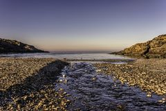 Pebble beach with a stream of water flowing into a still sea under blue skies. In Rumeli Feneri area, Black Sea, Sariyer, Istanbul, Turkey Royalty Free Stock Photo