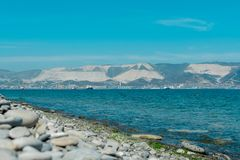Pebble beach on a summer day, mountains and sea on the background, port of Novorossiysk stock image