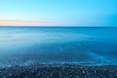 Pebble beach on a sunset with blurred seawater and horizon on a background. Copy space royalty free stock images