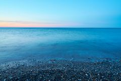 Pebble beach on a sunset with blurred seawater and horizon on a background. Copy space royalty free stock photography