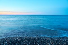 Pebble beach on a sunset with blurred seawater and horizon on a background. Copy space royalty free stock photo