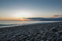 Pebble beach at sunset. Pebble beach. Calm sea. Setting sun. Distant mountains in clouds Royalty Free Stock Image