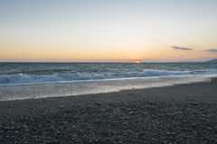 Pebble beach at sunset. Stormy sea. Waves Stock Image