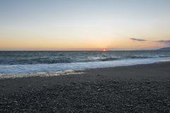 Pebble beach at sunset. Stormy sea. Waves Stock Photos