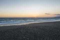 Pebble beach at sunset. Stormy sea. stock image