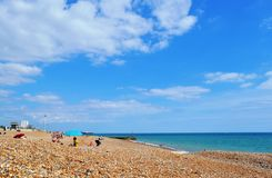 Pebble beach with tourists at Brighton in hot summer day. stock photos