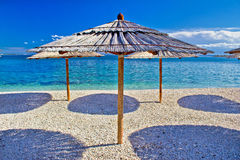 Pebble beach and turquoise sea umbrella Stock Photo